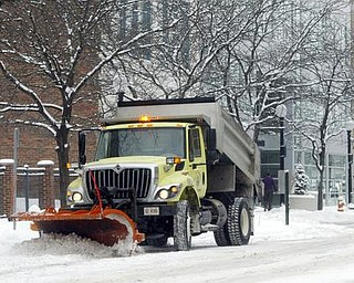 William D. Lewis/The Vindicator  A snow plow makes it way along Federal St in downtown Youngstown Friday morning.