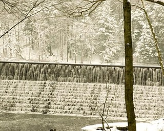 Water flows over the dam near the Pioneer Cabin in Mill Creek MetroParks.