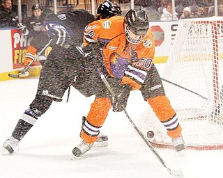 ON THE BRIGHT SIDE: Youngstown Phantoms' Andrew Lamont (20) and Alex Lippincott (11) of the Fargo Force fight for the puck when the teams met Friday in the first of two games over the weekend at  the Covelli Centre. The Phantoms lost both matches, but Lamont was a bright spot in Saturday's contest, scoring both goals of the night to give him eight for the year.