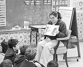 """Special to The Vindicator A LOT TO LEARN: As part of a community service project, Sarah Bivano, a student at Ursuline High School, recently spent some time with pupils in Mrs. Mellony Leonard's second-grade class at St. Patrick School In Hubbard. She reads the book """"If You Give a Moose A Muffin"""" to the youngsters. They listened attentively and learned about Alaska and Canada, where moose can be found. As a special treat, she gave each student a muffin and learned that if you give second-graders a muffin, it will make them happy."""