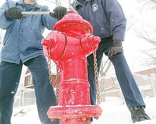 """SNOW JOB: Girard Fire Capt. Salvatore """"Sal"""" Ponzio, left, shows how a wrench is used to access a fire hydrant as firefighter Jim Quinn lends a hand. Girard water department maintains the hydrants and citizens cooperate by reporting any problems. If a hydrant should freeze, fire trucks carry 2,000 feet of hose to reach other hydrants and also carry a water supply."""