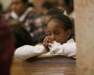 Mitchell Monroe prays for the victims of the Haiti's earthquake during a mass at the Cathedral of St. Mary's Wednesday Jan. 13, 2010, in Miami, Fla.'s Haitian community. (AP Photo/J. Pat Carter)