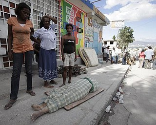 Women stand next to the body of a woman pulled from the wreckage left from the earthquake in Port-au-Prince, Wednesday, Jan. 13, 2010.