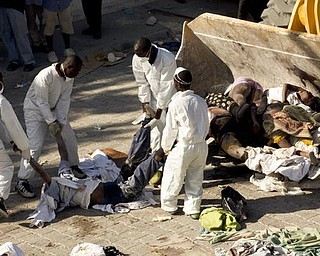 Workers move the bodies of the victims of the earthquake onto a bulldozer at the morgue in Port-au-Prince, Thursday, Jan. 14, 2010.