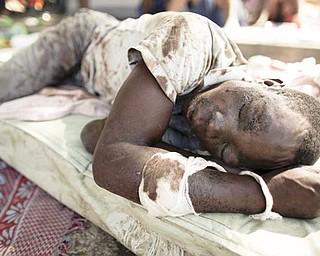 An earthquake survivor lies on a matt on a street of Port-au-Prince, Thursday, Jan. 14, 2010.