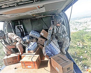 HELP FROM ON HIGH: U.S. troops drop food supplies from a helicopter as relief efforts continue throughout Port-au-Prince, Haiti. The 910th Airlift Wing at the Youngstown air base will join the humanitarian mission this week.
