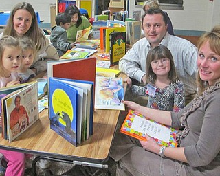 Dobbin's Literacy Night is not just for kids, it's a family affair. Parents are reminded of how fun animated stories can be. Sudha Rabindra (left) and mother Ashlin Rabindra are in the background reading. From front left: Kim Simon, Laurel Simon, Stacie Zarbaugh, Jeff Simon, Zoe Simon and Kim  Simon.