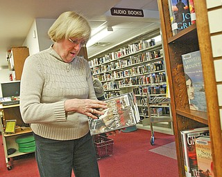 BACK IN THE LIBRARY: Jan Schaller, a former employee who was laid off from Hubbard Area Public Library because of budget cuts, returned as a volunteer. Here, she shelves books. Schaller said the volunteers help keep library services available.