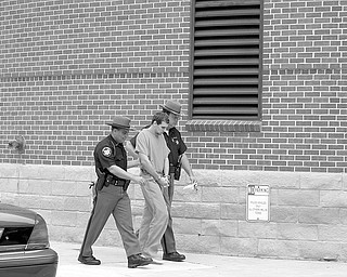 IN CUSTODY: Damion C. Wise, 30, in handcuffs and escorted by Trumbull County Sheriff's deputies in this file photo, was arrested Aug. 22, 2009, after a caller told police about Wise's 8-year-old stepson's injuries. The boy later told police Wise had beaten him with a small baseball bat and his fist, stuck his fingers down the boy's throat and threatened to maim or kill him.