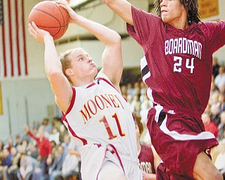 TOUGH ANGLE: Cardinal Mooney's Cy Schuster (11) goes up for a layup as Boardman's Dayne Hammond defends during the first quarter of a game at Mooney High School on Tuesday evening.