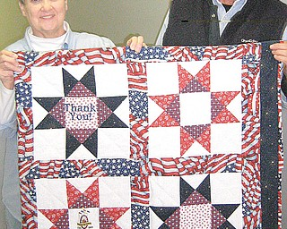 THANKING VETS: Columbiana County Fair Board members Sharen Cope, left, and Robert Crosser want sewers at this year's fair to make their entries a thank-you to wounded veterans. They ask that entries be red, white and blue and display a replica of the Purple Heart, the citation given to military personnel wounded in action.