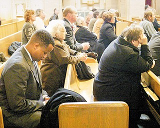 LET US PRAY: Youngstown Mayor Jay Williams bows with parishioners during the Mass. Fimognari's funeral was later Wednesday morning at St. Charles Church in Boardman.