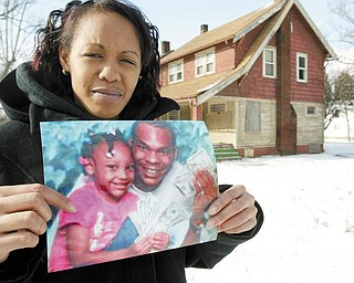 SOMBER REMINDER: It has been three years since the shooting deaths of four people at a South Side home. Police have made no arrests, and family members of the victims still have no answers. Dasha Burley, the mother of victim Anthony Crockett, holds a picture of Crockett and his daughter, Antanasia Crockett. In the background is the vacant West Evergreen Avenue house where the shootings occurred.