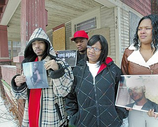 ASKING FOR HELP: Relatives of murder victims are asking the public to provide police with information leading to the arrest of the killers. The relatives are standing in front of the Evergreen Avenue home where the shootings took place. From left, De'Andre Parker, holding a picture of Danielle Parker, Dwayne Boone, LaShanda Boone and Shanell Boone, holding a picture of Marvin Boone. Danielle Parker, Marvin Boone, Anthony Crockett and Christopher Howard were killed.