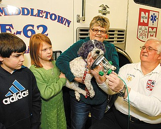 KEEPING PETS SAFE: Demonstrating the new oxygen mask for pets donated by Invisible Fence are, from left, Cole Smith, 10; Paige Smith, 8; Buddy, the cockpoo who is being held by his owner and their grandmother, Janet Smith of New Middletown; and Bill Opsitnik, New Middletown fire chief.