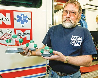 RANGE OF SIZES: Larry Culler, assistant chief of the New Middletown Fire Department, shows the three sizes of pet oxygen masks to accommodate different pets. The masks fit over an animal's muzzle and tubing directs air from an oxygen tank to the animal.