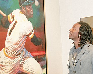 LIFE IMITATES ART: Pittsburgh Pirates center fielder Andrew McCutchen looks at a painting of Hall of Famer Roberto Clemente that hangs at The Butler Institute of American Art on Wick Avenue. McCutchen was in town Thursday with the Pirates Caravan, which stops annually at the museum. Some 200 fans attended.