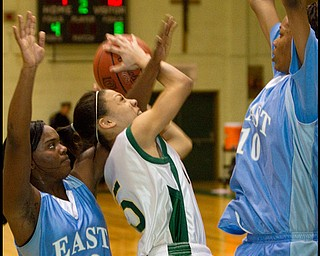 The Vindicator/Geoffrey Hauschild.Ursuline's Aurielle Irizzary (5) takes a shot while defended by East's Lesa Monet Oliver (22) and Briana Dawson (10) during the second quarter of a game at Ursuline High School on Thursday evening.