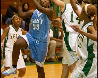 The Vindicator/Geoffrey Hauschild.East's Chelsea Bennett (23) is fouled while defended by Ursuline's Ja'Niece Whitehead (14) and Dominique Jenkins (15) during the second quarter of a game at Ursuline High School on Thursday evening.