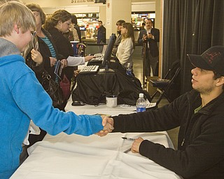 Spencer Patrick (13) of Columbiana shakes hands with Pittsburgh Penguins Center Tyler Kennedy (48) at his meet and greet with fans at Covelli Centre Friday evening before the Phantoms game against the Sioux Falls Stampede.