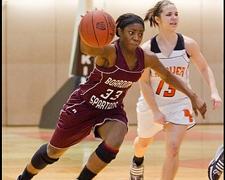 The Vindicator/Geoffrey Hauschild.Boardman's Doriyon Glass (33) drives down court past Hoover's Hannah Romano (13) during the fourth quarter of a game at Hoover High School on Saturday afternoon.