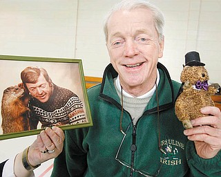 GROUNDHOG BUDDY: The Rev. Timothy O'Neill, pastor of St. Patrick Church in Hubbard, holds mementos of Groundhog Days past. The photo of him with Phil was taken in Punxsutawney about 25 years ago.