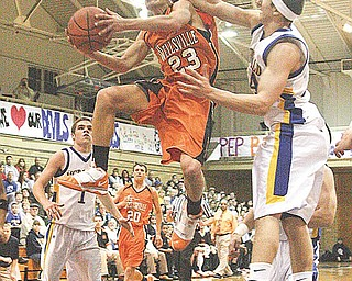 Michael Johnson (23) gets fouled on the way to the hoop by (24) Matthias Tayala during their game Tuesday night in McDonald.