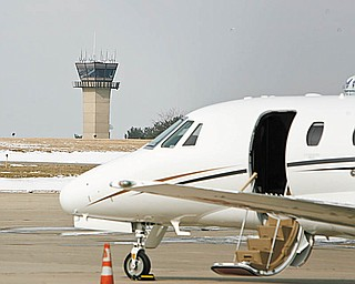 CHANGE ON HORIZON? A private jet sits at Winner Aviation at Youngstown-Warren Regional Airport with the FAA control tower in the background. The Federal Aviation Administration is proposing to move some air traffic controllers at the regional airport in Vienna to Cleveland Hopkins Airport.