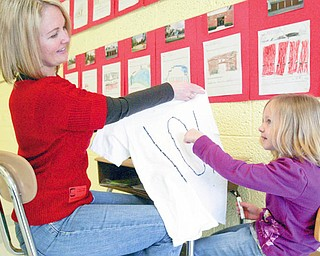 PARENTAL HELP: Deanna McIntosh, a parent volunteer at Joshua Dixon Elementary School in Columbiana, helps her daughter, Mandy, with a T-shirt project at school. Deanna is one of more than 60 parent volunteers at the school.