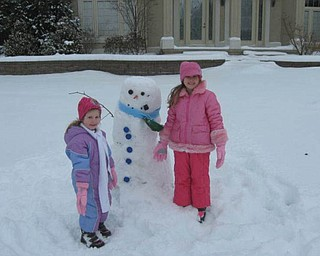 Alyssa Dill, 6, along with her sister Camie Dill, 3, have some winter time fun building a snowman at their house in Canfield. It was a great way to spend the day off of school.