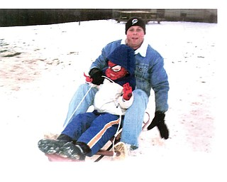 Eric Schenk and his son, Zane, of Lowellville take a ride on their old-fashioned red sled down Sled Hill in Mill Creek Park on Christmas Eve afternoon..