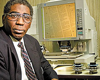 Steffon Jones sits along a microfilm machine at YSU's Maag Library. Jones and others have been using old newspaper articles and government documents to research a prominent local African American, Ferdinand H. Simpson.