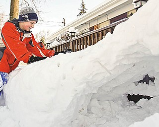 Tyler Evans (10) of Austintown packs more snow on top of the fort his father help him make.