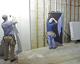 CLEAR VIEW: David Michael, left, and James Wolfe are both employees of Tri-State Glass in East Liverpool. They carried a large window into the soon-to-be Goodwill store in the Austintown Plaza. The store opening will mark the eighth Goodwill store for Youngstown Area Goodwill Industries.