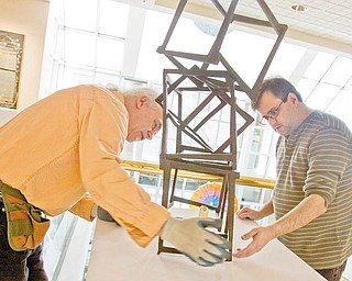 MEN AT WORK: Ed Hallahan, left, and Wayne Grover, workers at the Butler Institute of American Art on Wick Avenue, Youngstown, help stabilize Jedd Novatt's artwork. The art museum is a good place to spend time on a Valentine's Day date. The daily admission cost: free.
