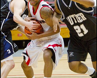 The Vindicator/Geoffrey Hauschild.YSU's Vance Cooksey (4) struggles past Butler's Zach Hahn (3) and Willie Veasley (21) and is ultimately fouled during the second half of a game at YSU's Beeghley Center on Thursday evening.