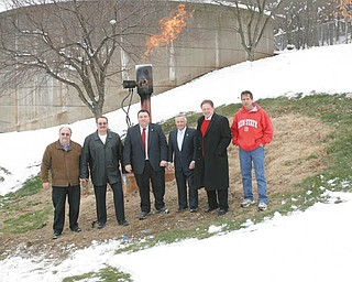 FREE FUEL: Officials stand in front of a flame of methane gas at the Struthers waste-treatment plant. The city and Mahoning County will save money when two new generators capture the methane and use it to power the plant. From left are: Gary DiOrio of MS Consultants, which designed the project; Tony Fire, 1st Ward councilman; county commissioners Anthony Traficanti and David Ludt; Struthers Mayor Terry Stocker; and plant manager Bob Gentile.