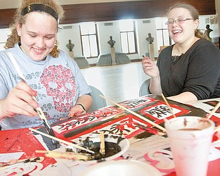 ANTI-PARTYING: Emerald Collins, 15, and Aree Adams, 14, both of Niles, paint during an anti-Valentine's Day party at the William McKinley Memorial Library in Niles on Thursday afternoon.