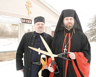 WELCOMING COMMITTEE: Father Anthony and Bishop Timothy cut the ribbon Thursday at the Monastery Inn in Canfield. The monastery is the former Canfield Colonial Motel and was purchased by monks from the Syro-Russian Orthodox Catholic Church who moved from the West Side of Cleveland. It includes short and long-term accommodations, a bookstore and gift shop and will eventually have a retreat center.