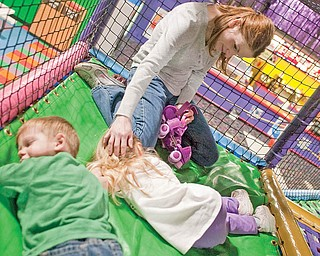 "The Vindicator/Geoffrey Hauschild.North Jackson resident, Sandy Virostek pats her three year-old daughter, Elizabeth's head as she lays down in the jungle gym alongside Jimmy Pegg, 2 of Vienna, at the Skate Zone in Austintown on Thursday afternoon. ""Its nice cause it wears them out and you can get them to bed on time,"" said Sandy of her first visit to the complex..1.21.2010.Skate Zone InFocus"