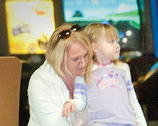 "The Vindicator/Geoffrey Hauschild.Stacie Gleichauf, of Austintown helps her daughter, Lillie, 3, with her skates at Skate Zone in Austintown on Thursday afternoon. ""We're excited to have somewhere to go in the winter,"" said Stacie about their first visit to the rink..1.21.2010.Skate Zone InFocus"