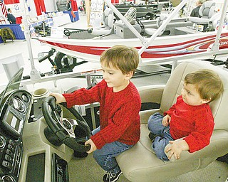 FUTURE CAPTAINS: Brothers James, 3, left, and Jonathan Smith, 21 months, sit in the captain's chair of a pontoon boat at the Penn-Ohio Boat Show at the Eastwood Expo Center in Niles on Sunday. The boys attended the weekend show with their father, Scott Smith of Boardman.