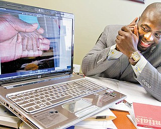 LENDING AN EAR AND A HELPING HAND: Dr. Michael Obeng spends time on the phone in his Boardman office offering services to a member of St. Elizabeth Medical Center's staff about helping those injured during the recent earthquake in Haiti. The computer shows the hand of a young patient of Obeng's born with six fingers. The doctor treated the child in Kumasi, Ghana, in 2009.