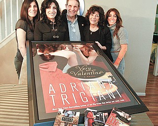 ALL IN THE FAMILY: Members of the Vechiarelli family, from left, daughters Amy Mancini and Beth Vechiarelli-Cooper, parents Dominic and Carol Vechiarelli and daughter Nanette Ungaro gather around a framed and signed poster of one of best-selling author Adriana Trigiani's books. One of the characters in Trigiani's last two books is named Dominic Vechiarelli for the Boardman man.