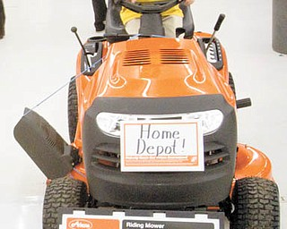 Noah Miller, 4 of Sandy Lake PA, sits atop a riding mower on display from The Home Depot during the Home and Garden Show at the Expo Center in Niles on Sunday afternoon.