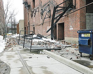 FALLEN STEEL: The steel frame of the fire escape outside the DeYor Performing Arts Center lies on the ground beneath the outline of where it once was on the building.