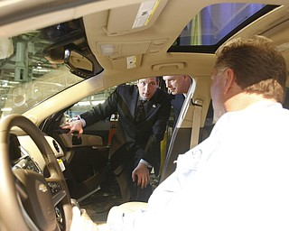 Robert K. Yosay /The Vindicator.Tim Ryan and Gov Ted Strickland  listen to Glen Johnson - VP 1112 tell about the features available on the CRUZE - 30-