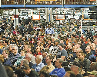 ALL EARS: Hundreds of employees at the GM Lordstown complex listen to Tuesday's announcement about the third shift. Production of the Chevrolet Cobalt, seen at the top, was halted for the ceremony.