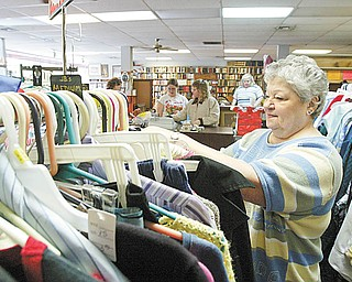 THRIFT STORE: Mary Henley straightens items in a rack at the Second Blessing Thrift Store in Salem. Henley is assistant manager of the store, which features clothes, used appliances and more.