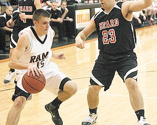 GIRARD - MINERAL RIDGE - (15) Zachary Kiger tries to drive as (23) Joe Augustine plays defense during their game Monday night. - Special to The Vindicator/Nick Mays